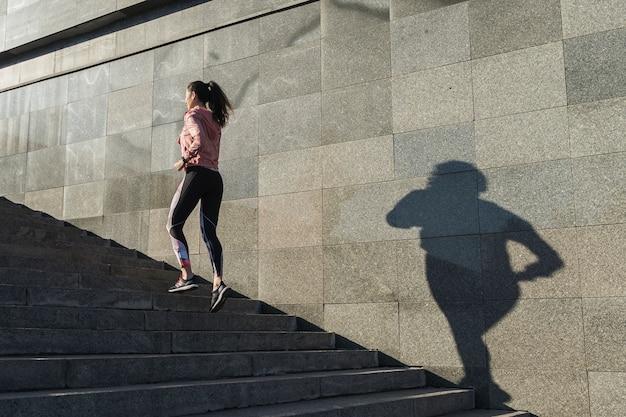 Jovem mulher correndo nas escadas Foto gratuita