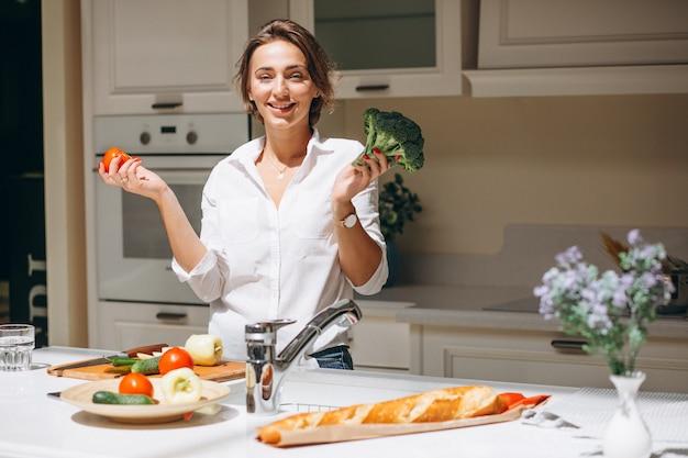 Jovem mulher cozinhando na cozinha pela manhã Foto gratuita