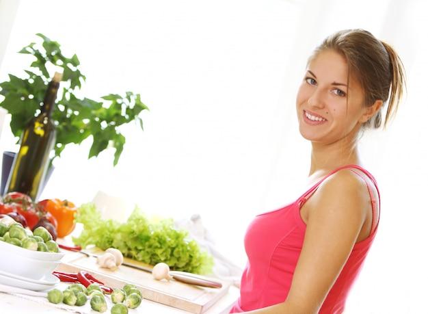 Jovem mulher cozinhar alimentos saudáveis Foto gratuita