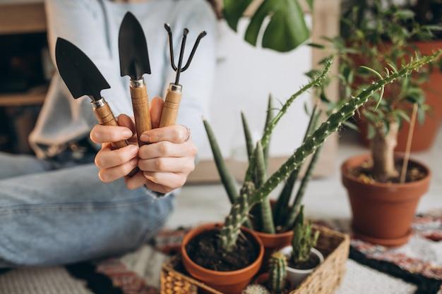 Jovem mulher cultivando plantas em casa Foto gratuita