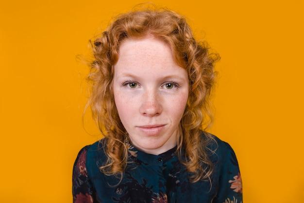 Jovem mulher curly do gengibre que olha a câmera Foto gratuita