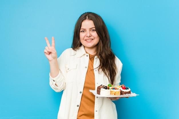 Jovem mulher curvilínea segurando um doce bolos mostrando o número dois com os dedos. Foto Premium
