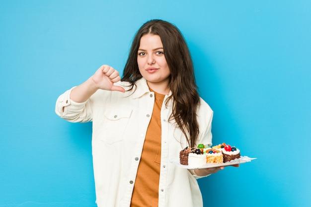 Jovem mulher curvilínea segurando um doce bolos sente-se orgulhoso e auto-confiante, exemplo a seguir. Foto Premium