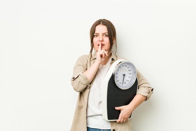Jovem mulher curvilínea segurando uma balança, mantendo um segredo ou pedindo silêncio. Foto Premium