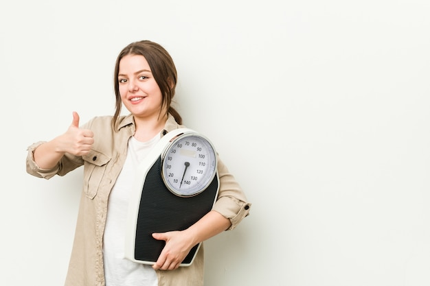 Jovem mulher curvilínea segurando uma balança sorrindo e levantando o polegar Foto Premium