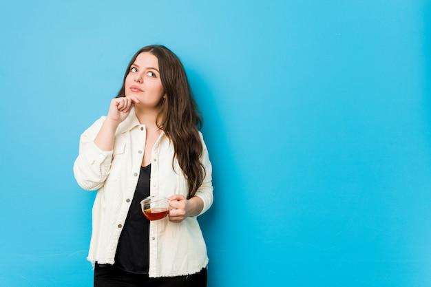 Jovem mulher curvilínea segurando uma xícara de chá, olhando de soslaio com expressão duvidosa e cética. Foto Premium