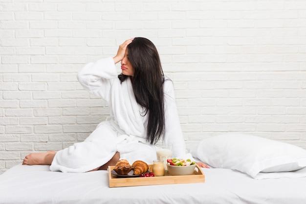 Jovem mulher curvilínea tomando um café da manhã na cama esquecendo algo, batendo na testa com a palma da mão e fechando os olhos. Foto Premium