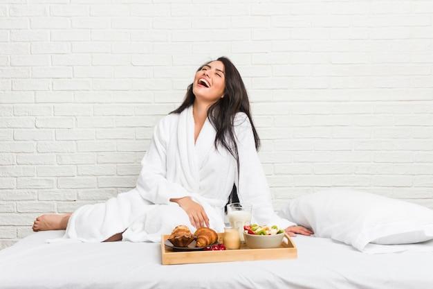 Jovem mulher curvilínea tomando um café da manhã na cama relaxada e feliz rindo, pescoço esticado, mostrando os dentes. Foto Premium