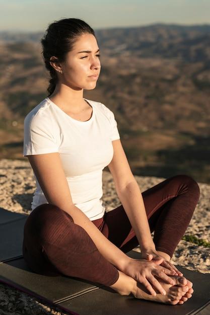 Jovem mulher de alto ângulo meditando Foto gratuita