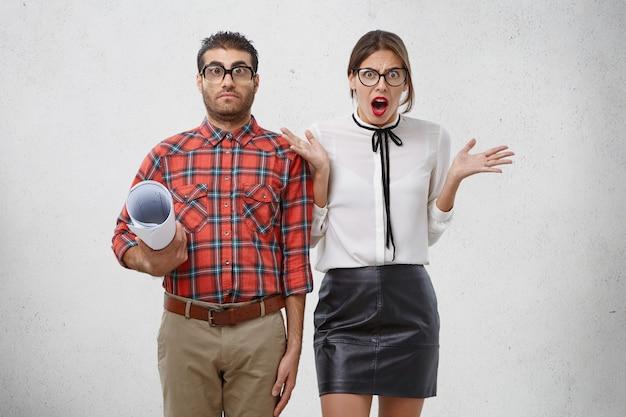 Jovem mulher de aparência agradável irritada com um colega, gesticula em descontentamento Foto gratuita
