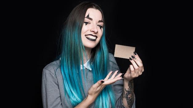 Jovem mulher de cabelo azul mostrando cartãozinho Foto gratuita