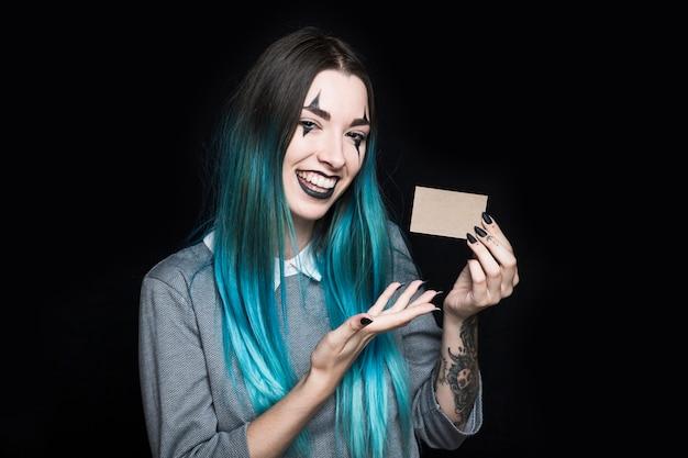 Jovem mulher de cabelo azul, segurando o cartão de papel Foto gratuita