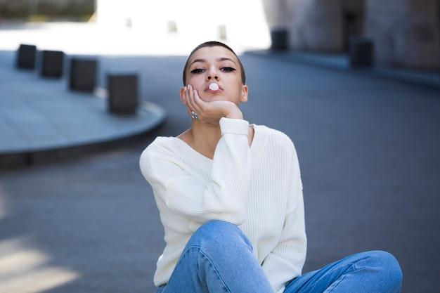 Jovem mulher de cabelo curto soprando goma Foto gratuita