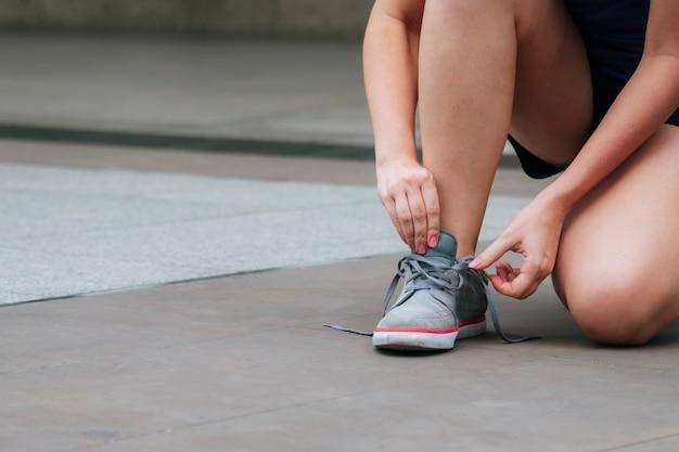 Jovem mulher de calçado de tênis esporte ajoelhou-se a fazer o cadarço. pronto para tênis de corrida em pessoa de corrida de exercício de esporte. feche as mãos amarrar os cadarços do corredor no estilo de vida de pessoa saudável de ginásio de fitness. Foto Premium