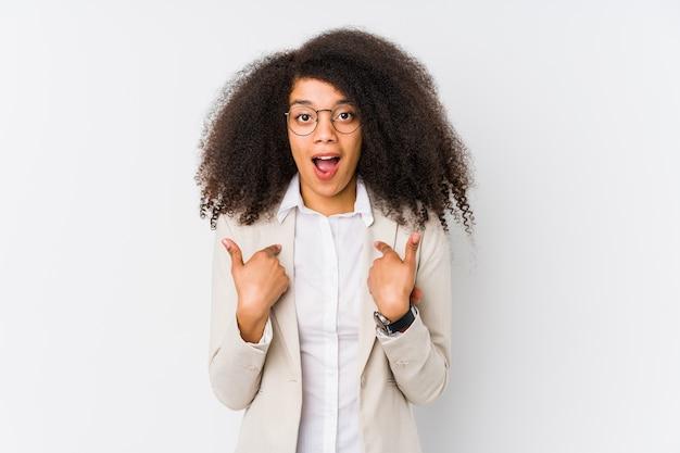 Jovem mulher de negócios afro-americana surpresa apontando com o dedo, sorrindo amplamente. Foto Premium