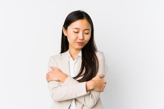 Jovem mulher de negócios chinesa isolada abraços, sorrindo despreocupada e feliz Foto Premium