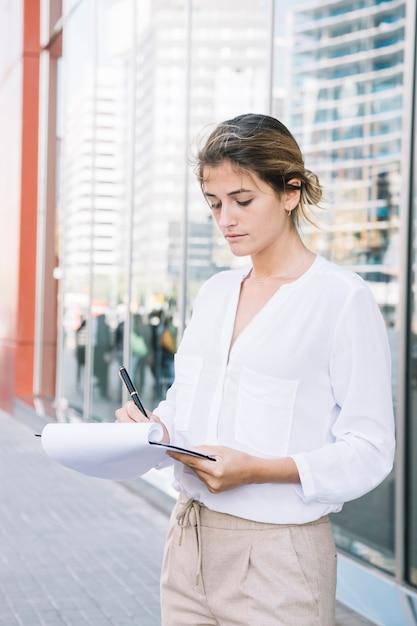 Jovem mulher de negócios, escrevendo na área de transferência com caneta Foto gratuita