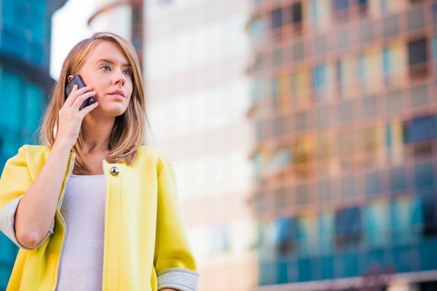 Jovem mulher de negócios fazendo um telefonema no telefone inteligente Foto gratuita