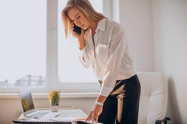 Jovem mulher de negócios usando telefone no escritório Foto gratuita