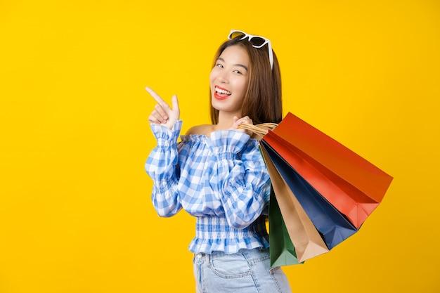 Jovem mulher de sorriso asiática atrativa que leva um saco coloful da compra e que aponta a propaganda da venda na parede, espaço da cópia e estúdio amarelos isolados, conceito preto da venda da estação de sexta-feira. Foto Premium