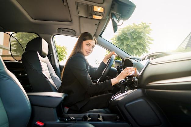 Jovem mulher de sorriso bonita no terno de negócio preto que conduz o carro, menina atrativa que senta-se no automóvel, fora retrato do verão. Foto Premium