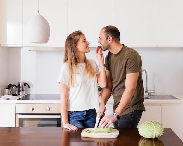 Jovem mulher de sorriso que alimenta a salada a seu marido na cozinha Foto gratuita