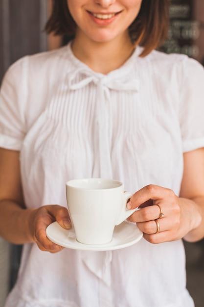 Jovem mulher de sorriso que guarda o copo do café saboroso Foto gratuita