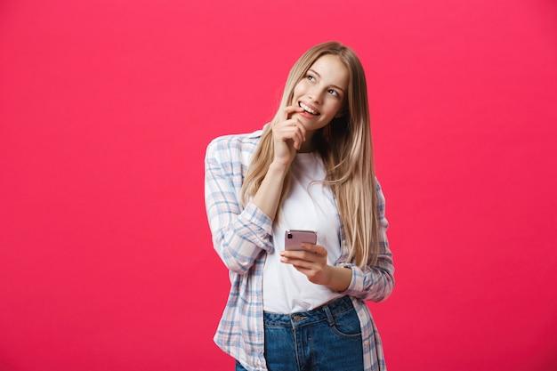 Jovem mulher de sorriso que pensa ao usar o smartphone. Foto Premium