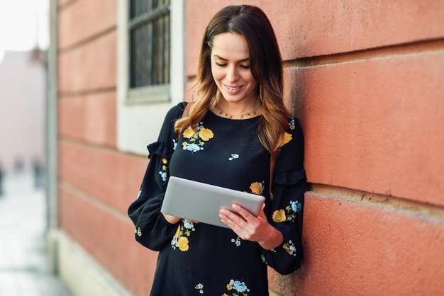 Jovem mulher de sorriso que usa a tabuleta digital ao ar livre. Foto Premium