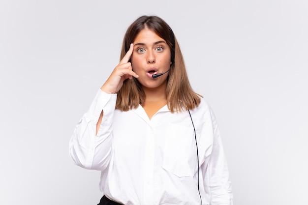 Jovem mulher de telemarketing parecendo surpresa, boquiaberta, chocada, percebendo um novo pensamento, ideia ou conceito Foto Premium