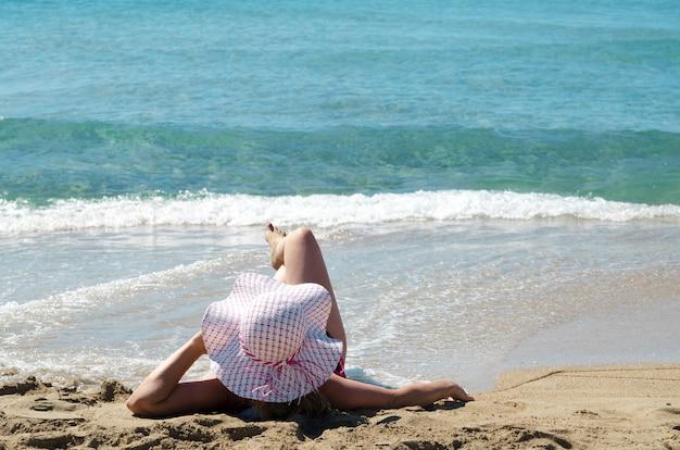 1898f0f44e Jovem mulher de volta, deitada com chapéu de sol na praia de areia e  aproveite
