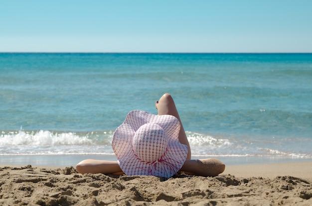 162775a82e Jovem, mulher de volta na cabeça, chapéu de sol na praia de areia e ...