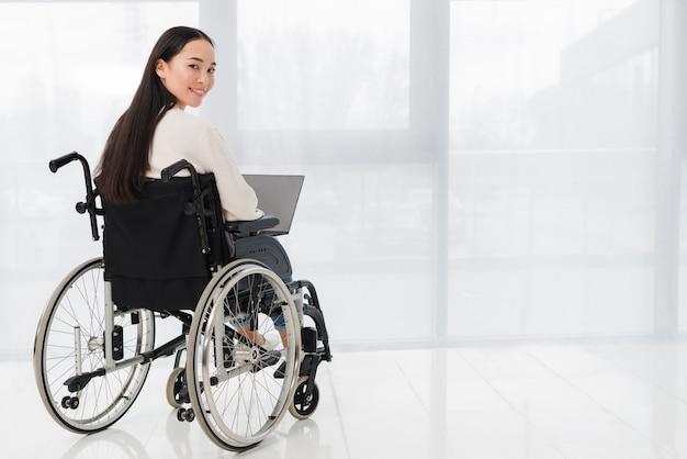 Jovem mulher deficiente que usa o portátil que olha sobre o ombro Foto Premium