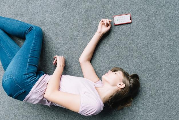 Jovem mulher deitada inconscientemente no tapete perto de telefone inteligente Foto gratuita