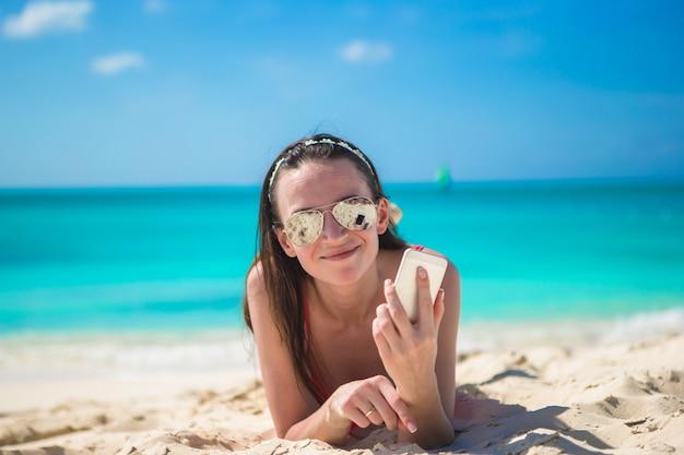 Jovem mulher deitada na areia branca e falando pelo telefone dela Foto Premium