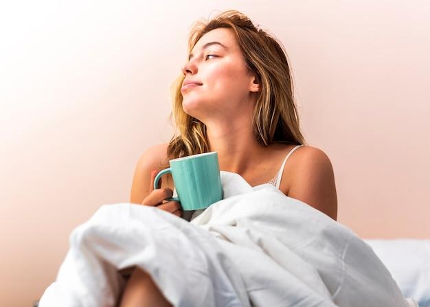Jovem mulher deitada na cama e olhando para longe Foto gratuita