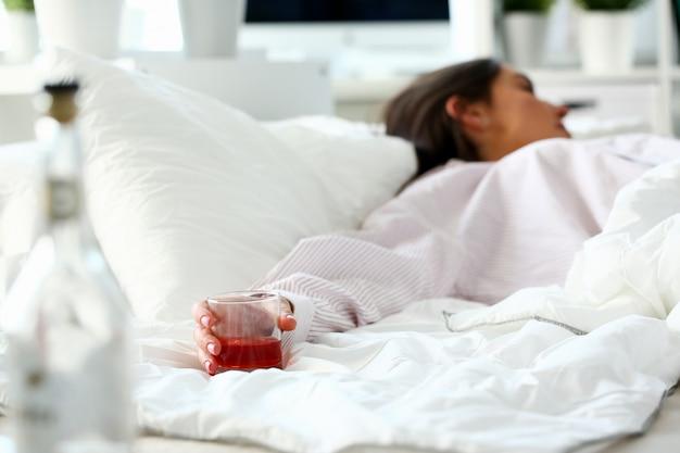 Jovem mulher deitada na cama mortalmente bêbada Foto Premium
