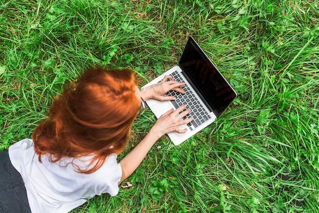 Jovem mulher deitada na grama brilhante com laptop Foto gratuita