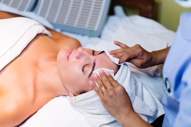 Jovem mulher deitada na mesa do cosmetologista durante o procedimento de rejuvenescimento Foto gratuita