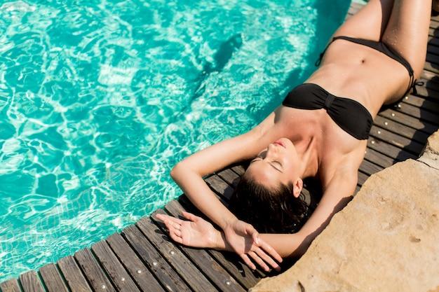 Jovem mulher deitada na piscina Foto Premium