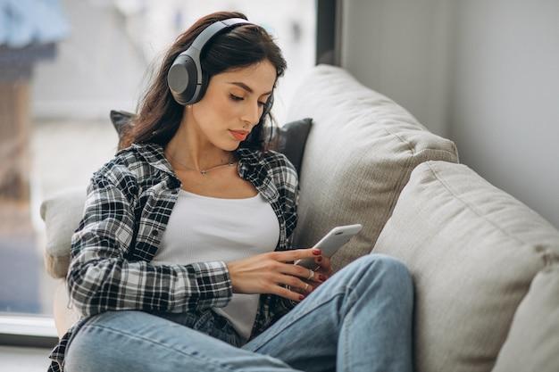Jovem mulher deitada no sofá em fones de ouvido, ouvindo música Foto gratuita