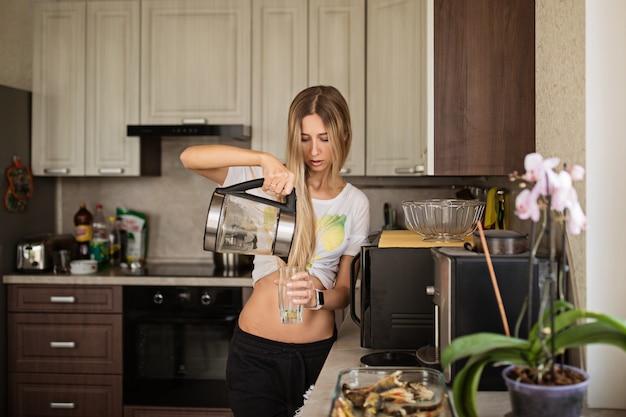 Jovem mulher derramando água no copo na cozinha Foto Premium