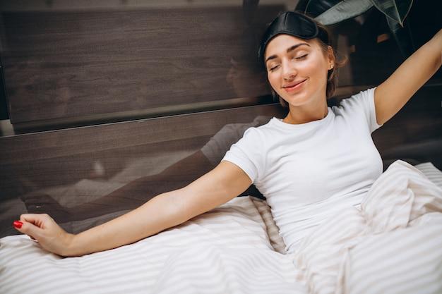Jovem mulher descansando na cama de manhã Foto gratuita