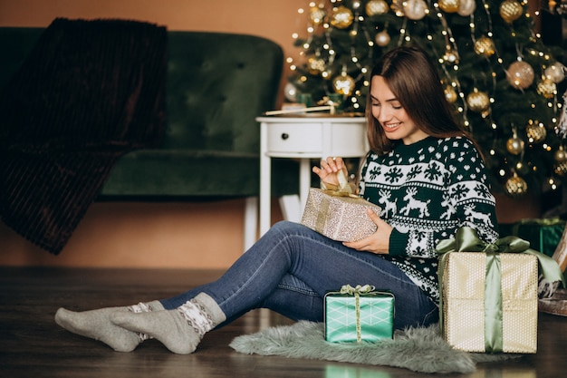 Jovem mulher desembalar presente de natal pela árvore de natal Foto gratuita