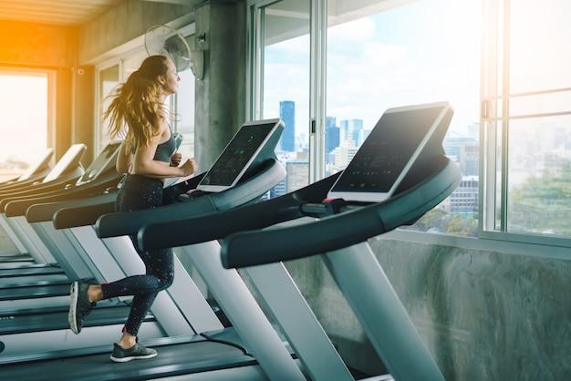 Jovem mulher desportiva alongamento no ginásio Foto Premium