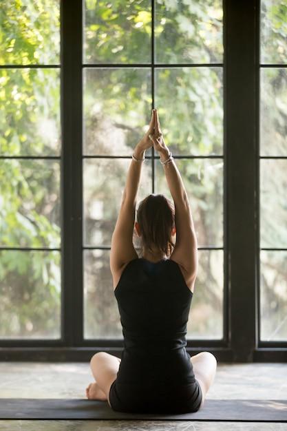 Jovem mulher desportiva em sukhasana pose, fundo de janela Foto gratuita