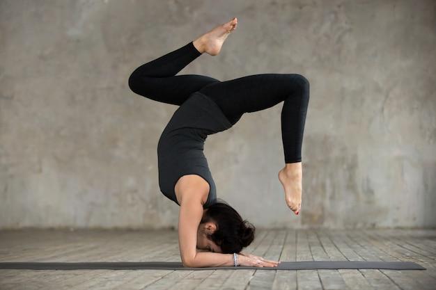 Jovem mulher desportiva fazendo exercício pincha mayurasana Foto gratuita