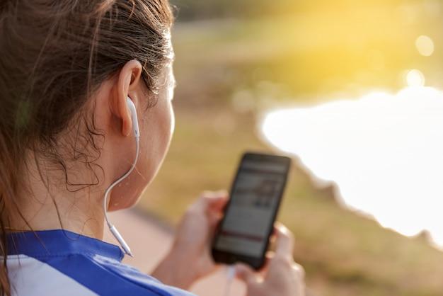 Jovem mulher desportiva ouve música através de um smartphone e fones de ouvido Foto Premium