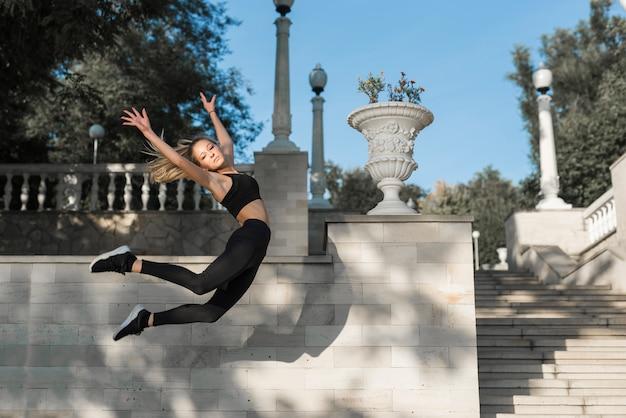 Jovem mulher desportiva pulando Foto gratuita