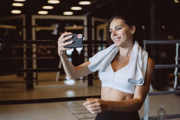 Jovem mulher desportiva tomando uma selfie com telefone móvel para redes sociais no ginásio. Foto gratuita